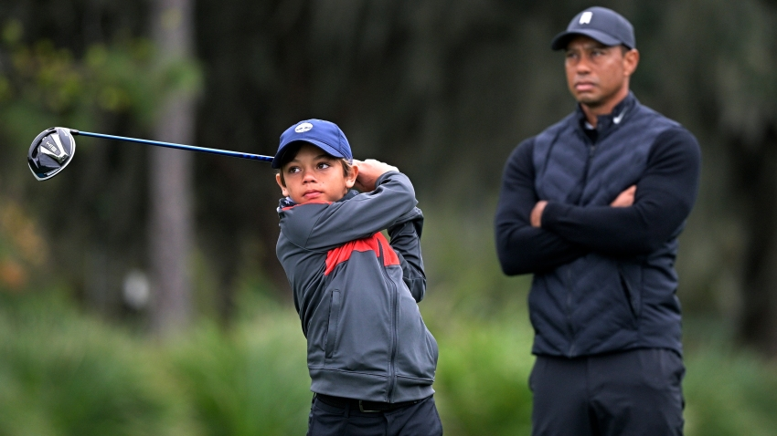 Tiger Woods, right, watches as his son Charlie tees off on the 12th hole during a practice round of the Father Son Challenge golf tournament, Thursday, Dec. 17, 2020, in Orlando, Florida.