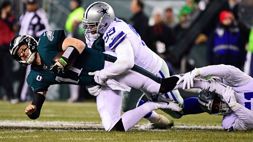 Carson Wentz #11 of the Philadelphia Eagles is tackled by Antwaun Woods #99 of the Dallas Cowboys and Kerry Hyder #51 during the second quarter at Lincoln Financial Field on Dec. 22, 2019 in Philadelphia, Pennsylvania.