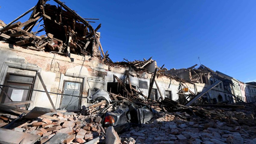 This photograph taken on December 29, 2020, shows the wreckage of a car and damaged buildings in Petrinja, some 50kms from Zagreb, after the town was hit by an earthquake of the magnitude of 6.4.