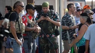 gun-carrying men wearing Hawaiian print shirts associated with the boogaloo movement watch a demonstration near where President Trump had a campaign rally in Tulsa, Okla