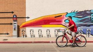 Man riding bike past Magnolia Station