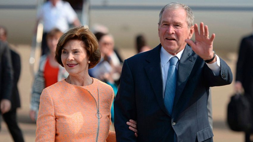 Former US President George W. Bush (R) waves to journalists next to his wife Laura (L) as they arrive for an official visit to Botswana, in Gaborone on April 4, 2017.