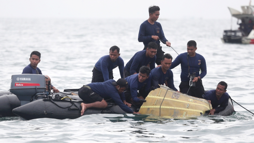Indonesian Navy divers pull out a part of an airplane out of the water during a search operation for the Sriwijaya Air passenger jet that crashed into the sea near Jakarta, Indonesia, Sunday, Jan. 10, 2021. Indonesian divers on Sunday located parts of the wreckage of the Boeing 737-500 in the Java Sea, a day after the aircraft with dozens of people onboard crashed shortly after takeoff from Jakarta.