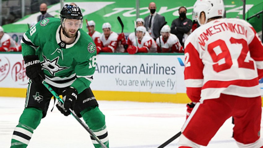 Jason Dickinson #18 of the Dallas Stars skates the puck against Vladislav Namestnikov #92 of the Detroit Red Wings in overtime at American Airlines Center on Jan. 26, 2021 in Dallas, Texas.