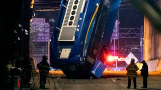 A bus in New York City which careened off a road in the Bronx neighborhood of New York and is left dangling from an overpass, Jan. 15, 2021, after a crash late Thursday that left the driver in serious condition, police said.