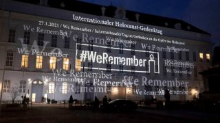 The words '#WeRemember' are displayed at the facade of the Austrian Parliament at the Hofburg palace in support of the campaign for the International Holocaust Remembrance Day in Vienna, Austria, Jan. 27, 2021.