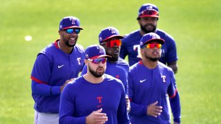 Texas Rangers outfielders from left, Leody Taveras, Joey Gallo, Adolis Garcia, Willie Calhoun and Delino DeShields, back right, run during spring training baseball practice, Friday, Feb. 26, 2021, in Surprise, Ariz.