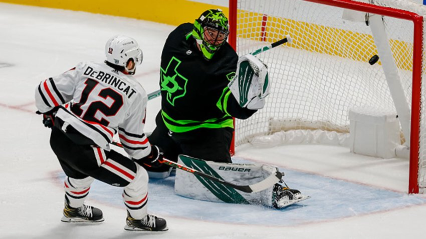 Chicago Blackhawks left wing Alex DeBrincat (12) scores a goal against Dallas Stars goaltender Jake Oettinger (29) in overtime to win the game between the Dallas Stars and the Chicago Blackhawks on Feb. 7, 2021 at American Airlines Center in Dallas, Texas.