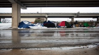 Homeless camps sit along the I-35 frontage road in Austin, Texas on February 17, 2021. Millions of Texans are still without water and electric as winter storms continue.
