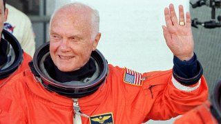 KENNEDY SPACE CENTER, UNITED STATES: US astronaut and senator John Glenn waves as he leaves the Operations and Check out building at the Kennedy Space Center, FL, 29 October in route to board the US space shuttle Discovery. The seven person crew will perform several scientific experiments during their nine day mission, including studies on the effects of weightlessness on 77-year-old Glenn. Glenn who is 77 years old will be the oldest man to fly into space. October 29, 1998