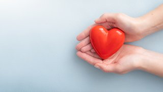 American Heart Month- Hands holding Heart