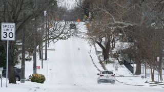 Vehicles travel on a snow-covered road in McKinney, Texas, Feb. 16, 2021.