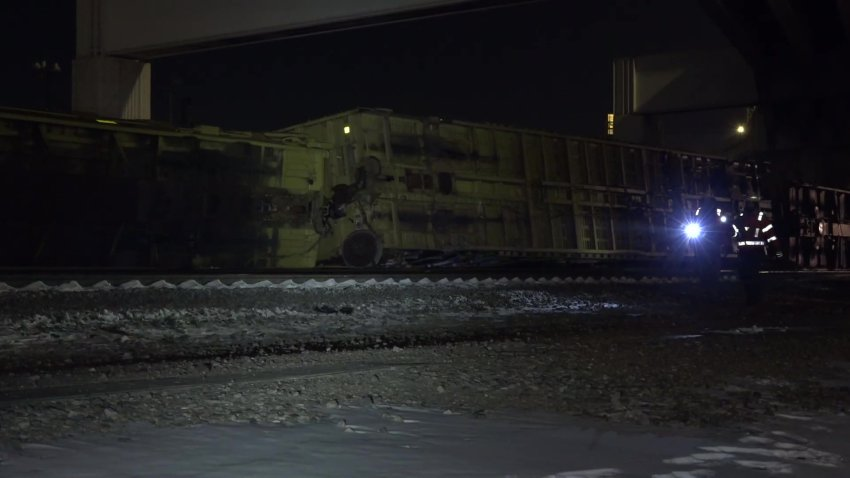 In the picture the train is seen laying on it's side of the railing.