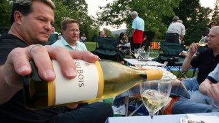 Michael Van Parks, left, pours wine with friends, Bill Beeman, center, and Don Usher, right, all of West Hartford, Conn., while having a picnic on the lawn at Tanglewood in Lenox, Mass