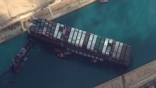 In this March 26, 2021, file photo, the cargo ship MV Ever Given is stuck in the Suez Canal near Suez, Egypt. A maritime traffic jam grew to more than 200 vessels Friday outside the Suez Canal and some vessels began changing course as dredgers worked frantically to free a giant container ship that is stuck sideways in the waterway and disrupting global shipping.