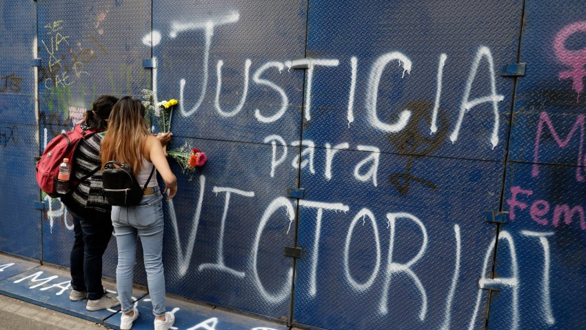"Young women place flowers on the perimeter wall of the Quintana Roo state offices sprayed with graffiti that reads in Spanish ""Justice for Victoria,"" during a protest in Mexico City, Monday, March. 29, 2021. The demonstrators were protesting the police killing in Tulum, Quintana Roo state, of Salvadoran national Victoria Esperanza Salazar when a female police officer knelt on her back to cuff her. Mexican authorities say an autopsy confirmed that police broke her neck."