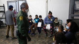 Migrants are processed at the intake area of the U.S. Customs and Border Protection facility, the main detention center for unaccompanied children in the Rio Grande Valley, in Donna, Texas, Mar. 30, 2021.