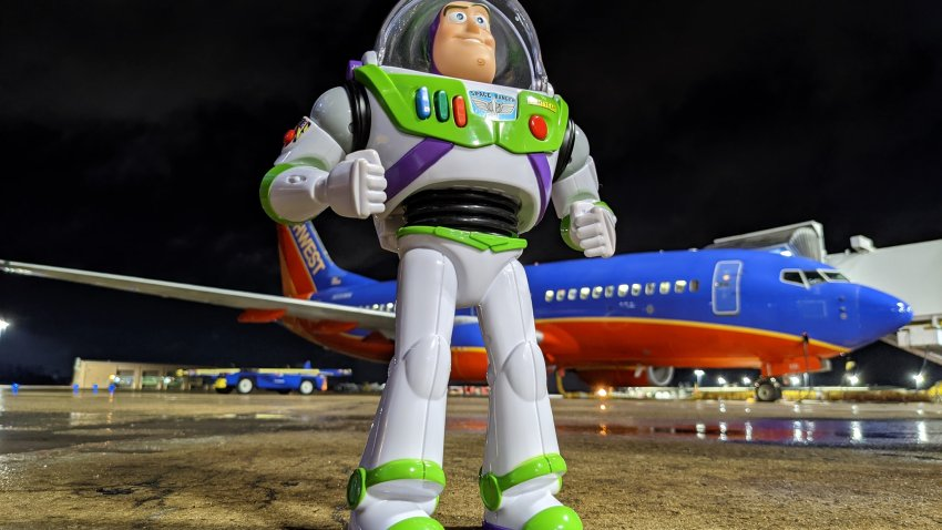 Buzz Lightyear toy in front of a Southwest plane