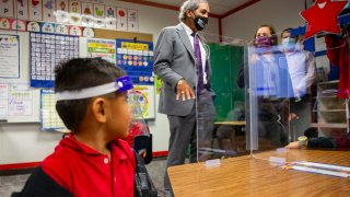 DISD Kindergartener looks up at teacher through clear mask and protective shield.