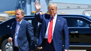 US President Donald Trump waves upon arrival, alongside Attorney General of Texas Ken Paxton (L) in Dallas, Texas, on June 11, 2020, where he will host a roundtable with faith leaders and small business owners.