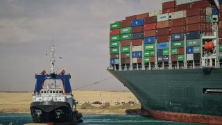 """A tugboat takes part in the refloating operation carried out to free the """"Ever Given"""", a container ship operated by the Evergreen Marine Corporation, which is currently stuck in the Suez Canal."""