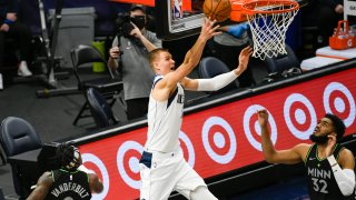 Dallas Mavericks center Kristaps Porzingis, center, releases a shot as Minnesota Timberwolves forward Jarred Vanderbilt (8) and center Karl-Anthony Towns (32) watch during the first half of an NBA basketball game Wednesday, March 24, 2021, in Minneapolis.