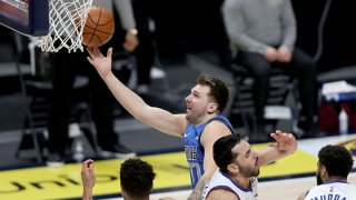 Luka Doncic #77 of the Dallas Mavericks goes to the basket against Michael Porter Jr. #1 and Facundo Campazzo #7 of the Denver Nuggets in the fourth quarter at Ball Arena on March 13, 2021 in Denver, Colorado.