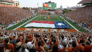 "FILE - Fans sing ""The Eyes of Texas"" before the start of the NCAA football game between the Texas Longhorns and the Rice Owls on Sept. 3, 2011, at Darrell K. Royal-Texas Memorial Stadium in Austin, Texas."
