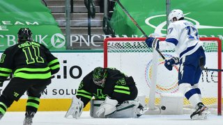 A shot gets through Anton Khudobin #35 of the Dallas Stars for a power play goal against the Tampa Bay Lightning at the American Airlines Center on March 23, 2021 in Dallas, Texas.