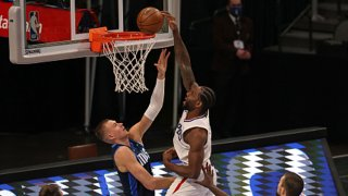 Kawhi Leonard #2 of the LA Clippers makes the slam dunk against Kristaps Porzingis #6 of the Dallas Mavericks in the fourth quarter at American Airlines Center on March 15, 2021 in Dallas, Texas.