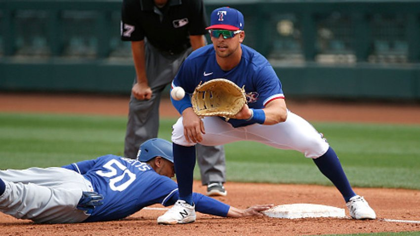 First baseman Nate Lowe #30 of the Texas Rangers fields a throw on a pick-off attempt of base runner Mookie Betts #50 of the Los Angeles Dodgers in the fourth inning of the MLB spring training baseball game at Surprise Stadium on March 7, 2021 in Surprise, Arizona.