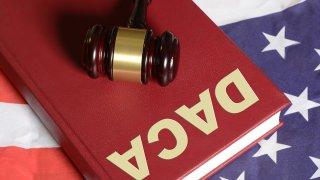 Foto de un libro que lee DACA con un mazo y la bandera de Estados Unidos.