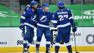 Pat Maroon #14, Ross Colton #79, Ryan McDonagh #27 and the Tampa Bay Lightning celebrate a goal against the Dallas Stars at the American Airlines Center on March 16, 2021 in Dallas, Texas.