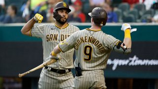 Eric Hosmer #30 of the San Diego Padres and Jake Cronenworth #9 of the San Diego Padres celebrate Hosmers solo home run against the Texas Rangers during the fourth inning at Globe Life Field on April 10, 2021 in Arlington, Texas.
