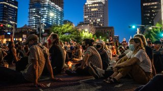 FILE: People sit in the street at a vigil for Garrett Foster on July 26, 2020 in downtown Austin, Texas. Garrett Foster, 28, who was armed and participating in a Black Lives Matter protest, was shot and killed after a chaotic altercation with a motorist who allegedly drove into the crowd. The suspect, who has yet to be identified, was taken into custody.