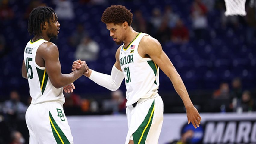 Davion Mitchell #45 and MaCio Teague #31 of the Baylor Bears clasp hands late in the game against the Arkansas Razorbacks in the Elite Eight round of the 2021 NCAA Division I Men's Basketball Tournament held at Lucas Oil Stadium on March 29, 2021 in Indianapolis, Indiana.