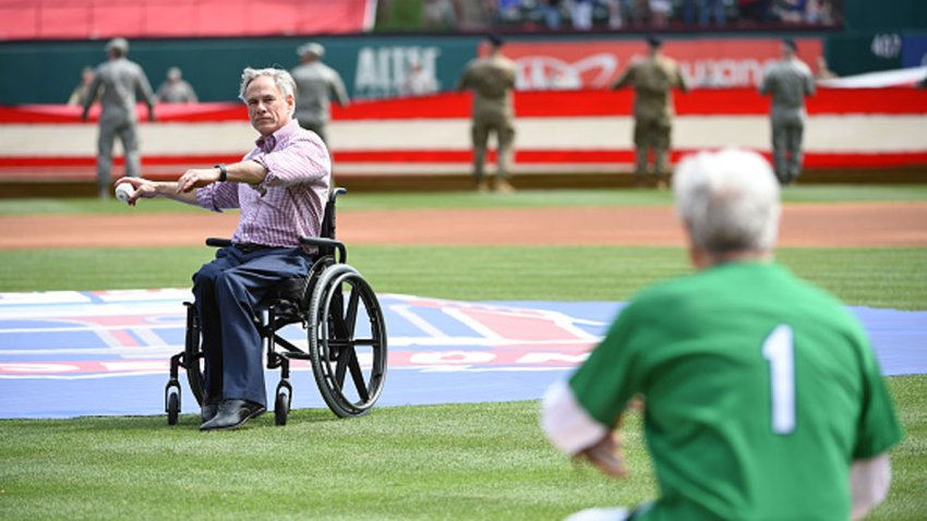 FILE: Texas Governor Greg Abbott throws out the ceremonial first pitch before the game between the Chicago Cubs and the Texas Rangers at Globe Life Park in Arlington on Thursday, March 28, 2019 in Arlington, Texas.
