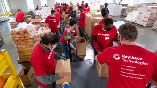 Multiple people in red Raytheon shirts pack up foods