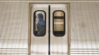 A passenger boards a train at Washington Metro's Dupont Circle station