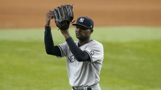 New York Yankees starting pitcher Domingo German taps his glove as he walks to the dugout after working against the Texas Rangers in the seventh inning of a baseball game in Arlington, Texas, Thursday, May 20, 2021.