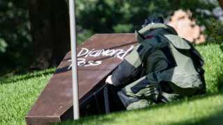 A bomb squad member investigates the coffin that was placed on Dallas County District Attorney John Creuzot's front lawn May 29, 2021.