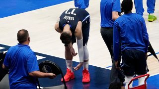 Dallas Mavericks guard Luka Doncic leans over as he heads to the bench during a timeout in fourth quarter of an NBA playoff basketball game against the LA Clippers at American Airlines Center on Friday, May 28, 2021, in Dallas.