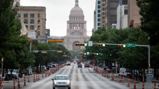 Cars drive on Congress Avenue in front of the Texas Capitol building on July, 14, 2020 in Austin, Texas. Only nine ICU beds were available Friday, July 30, in the 11-county trauma service region that includes Austin and serves 2.3 million people, according to the health department.