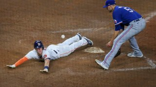 Houston Astros center fielder Myles Straw (3) avoids the tag at home plate and scores the winning run in the bottom of the eleventh inning during the baseball game between the Texas Rangers and Houston Astros on May 13, 2021 at Minute Maid Park in Houston, Texas.