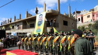 Members of the Iran-backed Hezbollah movement, surround the coffin of Mohamad Kassem Tahan, a fellow member killed a day earlier by Israeli shelling on the frontier with Lebanon during a protest against the latest assault on the Gaza Strip, at his funeral in the southern Lebanese village of Adloun, on May 15, 2021.