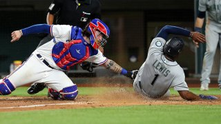 Jonah Heim #28 of the Texas Rangers stretches to make the tag on Kyle Lewis #1 of the Seattle Mariners for the final out of the game at Globe Life Field on May 8, 2021 in Arlington, Texas.