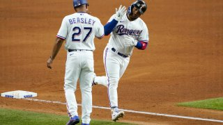 Texas Rangers third base coach Tony Beasley (27) celebrates with Willie Calhoun, right, as he runs home after hitting a solo home run off of New York Yankees starting pitcher Gerrit Cole in the fifth inning of a baseball game in Arlington, Texas, Monday, May 17, 2021.