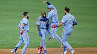 Adolis Garcia #53 of the Texas Rangers and teammates Jose Trevino #23, Isiah Kiner-Falefa #9 and Joey Gallo #13 celebrate Garcia's game winning walk-off RBI single against the Houston Astros at Globe Life Field on May 23, 2021 in Arlington, Texas. The Rangers won 3-2.