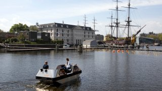 An electric boat steers close to a full-size replica of the 18th century three-mast trading ship Amsterdam at the National Maritime Museum, in Amsterdam, Thursday, May 20, 2021. Already steeped in maritime history, the city's more than 100 kilometers (60 miles) of waterways are to start hosting prototypes of futuristic boats — small, fully-autonomous electric vessels — to carry out tasks including transporting passengers and picking up garbage.