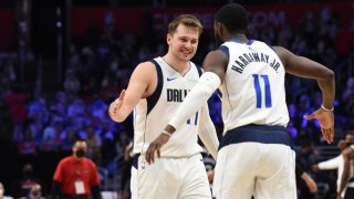 Luka Doncic #77 of the Dallas Mavericks high fives Tim Hardaway Jr. #11 of the Dallas Mavericks during Round 1, Game 5 of the 2021 NBA Playoffs on June 2, 2021 at STAPLES Center in Los Angeles, California.